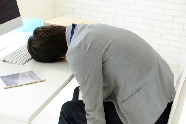 パソコン前で寝る男性