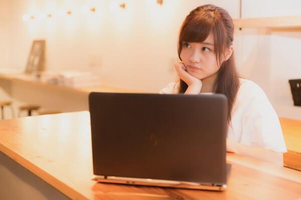 パソコン前で考え事をする女性